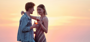 Couple standing with a drink at sunset